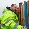 Trainee fence builder with spirit level