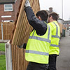 Trainee fence builders moving fence panels