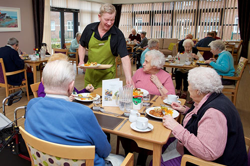 Waiter serving a meal to residents at Croftlands independent living extra care scheme